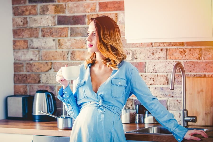 Woman drinking raspberry leaf tea to help with her pregnancy symptoms